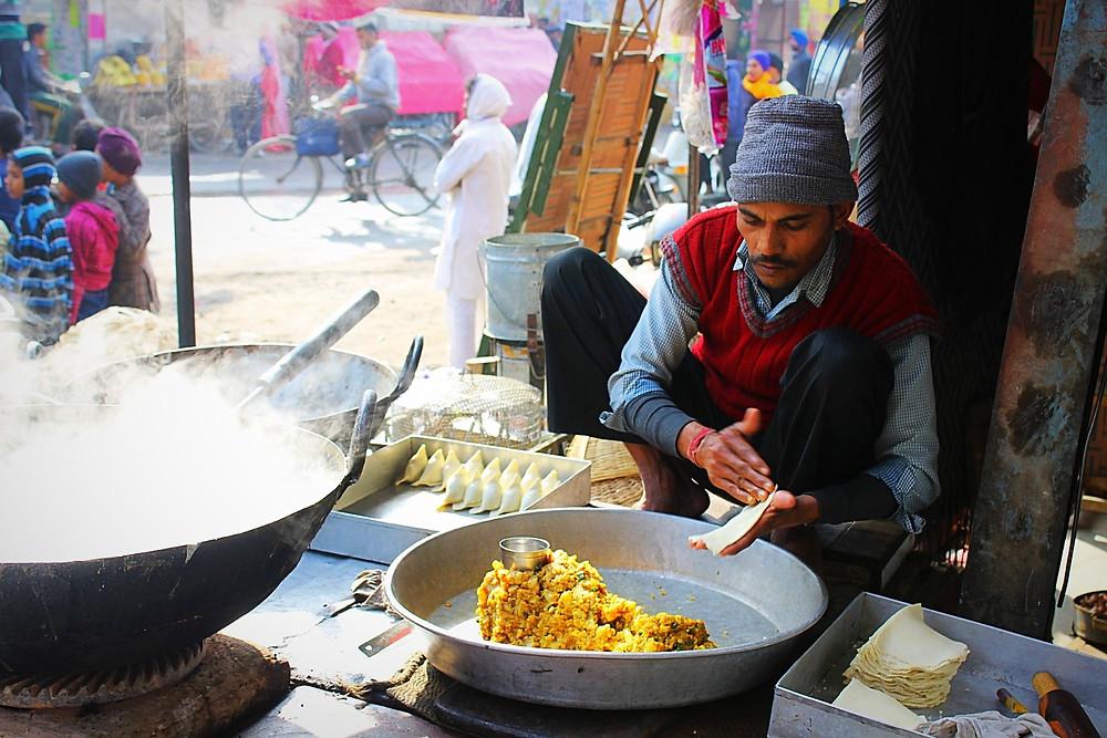 Indian street food vendor hand making samosas
