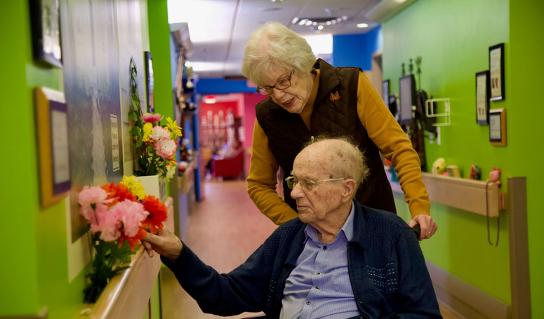 henley place resident and wife looking at flowers