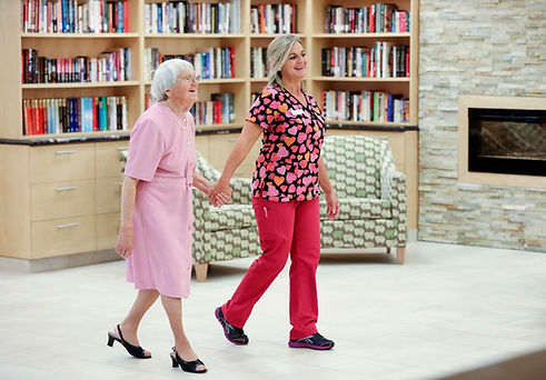 henley place resident and nurse holding hands walking in lobby