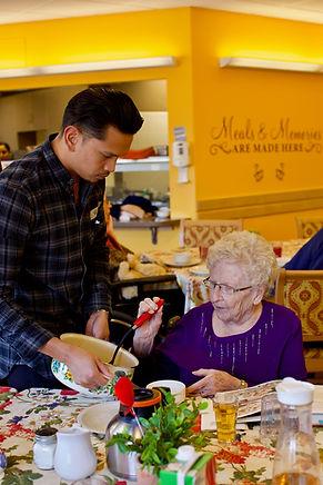 primacare volunteer serving food to senior resident