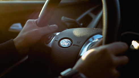 hands holdind a ford steering wheel