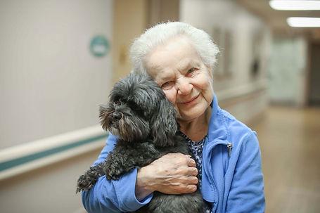 long term care resident hugging dog