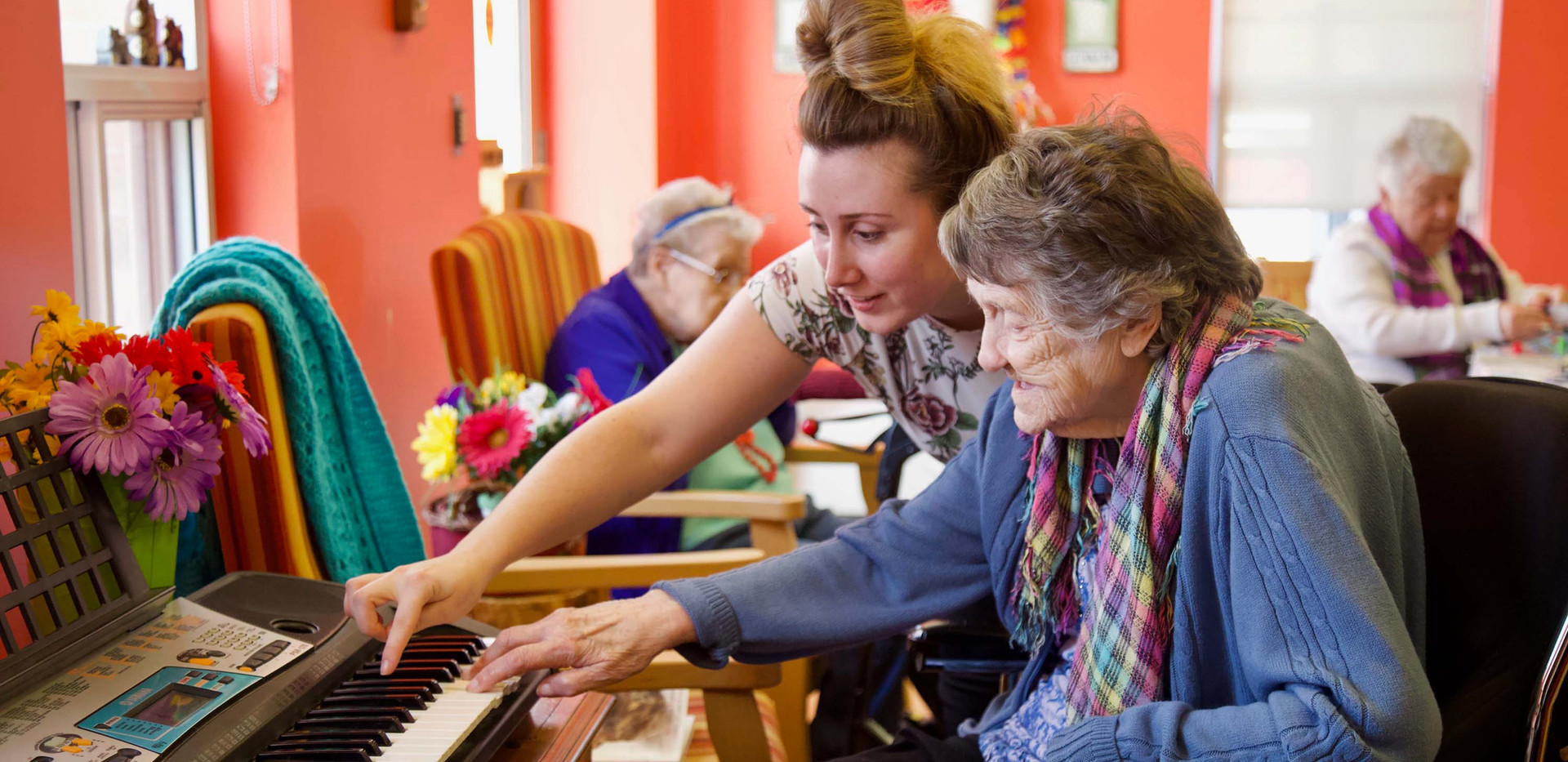 henley place resident and nurse playing the piano