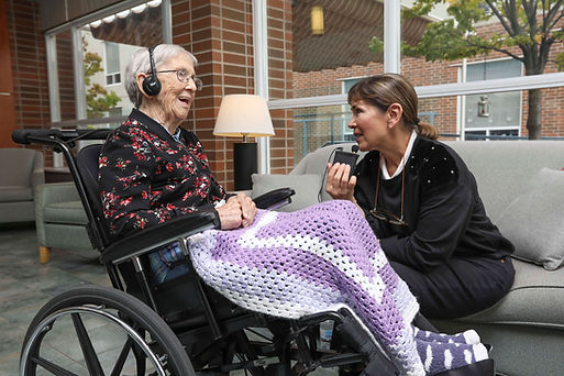 henley house resident with nurse listening to audio