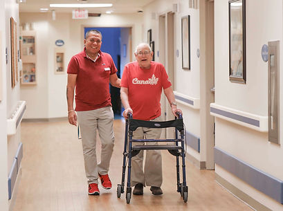 primacare staff member and resident walking in hallway