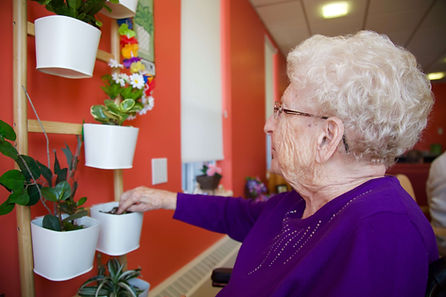 primacare resident checking plants in hallway