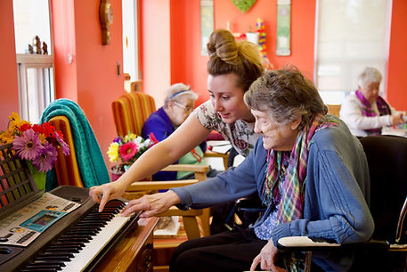primacare staff member playing piano with resident
