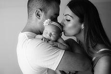 mother kissing newborn on daddy shoulder