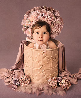 baby girl in bucket with floral headpiece