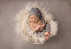 baby in bowl with grey hat and pants