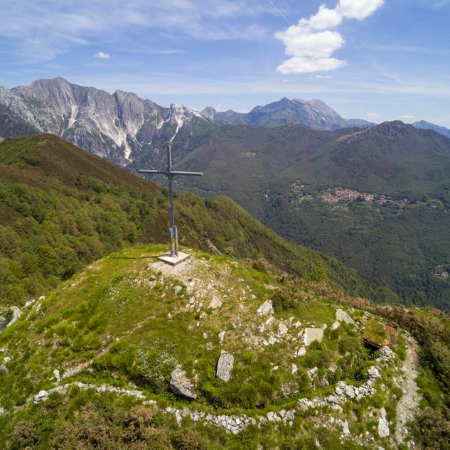 la vetta del Folgorito, sullo sfondo le Alpi Apuane, in basso una trincea