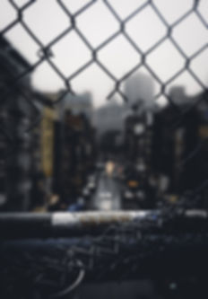 urban-view-through-cut-chain-link-fence_