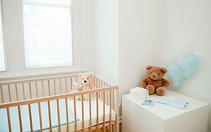 Light and bright baby nursery. Crib, balloons and teddy bear.