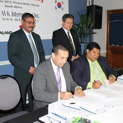 Adv Shaheed Patel (left) for the Kanaland Municipality and Hilton Slamit for MK International at the memorandum of understanding signing ceremony held at the King George Hotel. At the back, watching the proceedings, are Morné Hoogbard (left) and Dr Hae-Jung Jung. Photo: Myron Rabinowitz