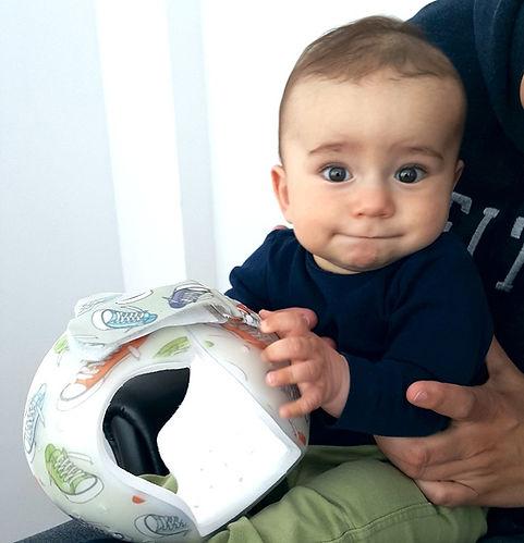dojenček s čelado v rokah