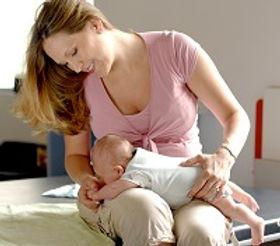 Otrok leži obrnjen z obrazem navzdol v starševem naročju