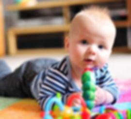 Otrok leži na odeji na trebuhu okoli njega pa igrače in ostale stimulacije