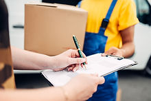 male-worker-in-uniform-gives-parcel-to-t