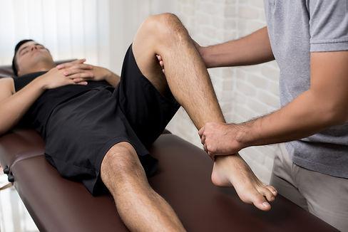 Therapist treating injured leg of athlet