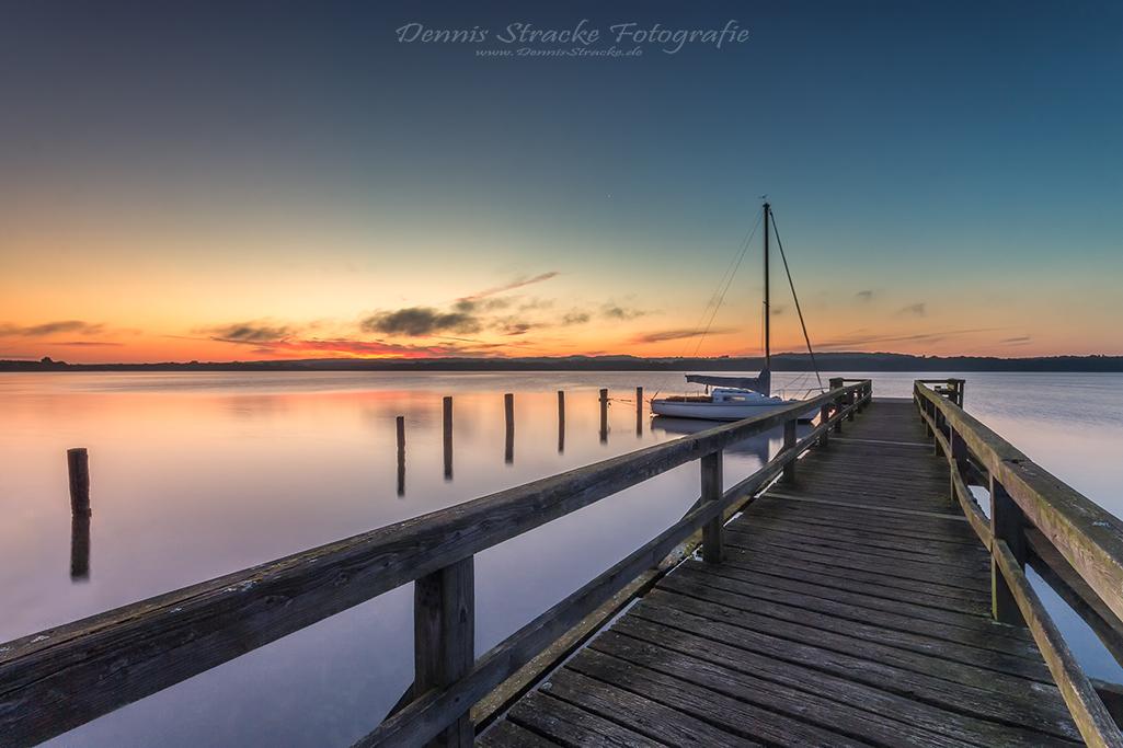 Segelboot am Steg zum Sonnenaufgang