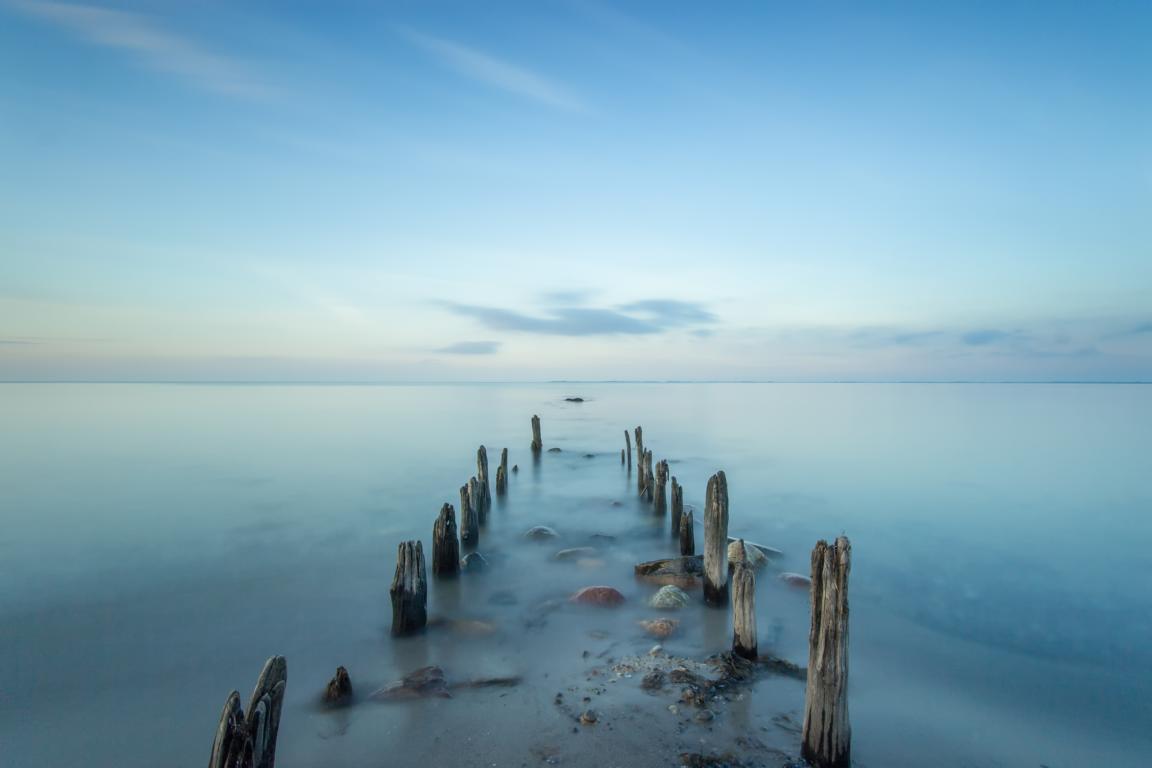 Holzbuhne und Steine am Ostseeufer