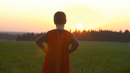 boy-with-superhero-cape-standing-in-a-fi