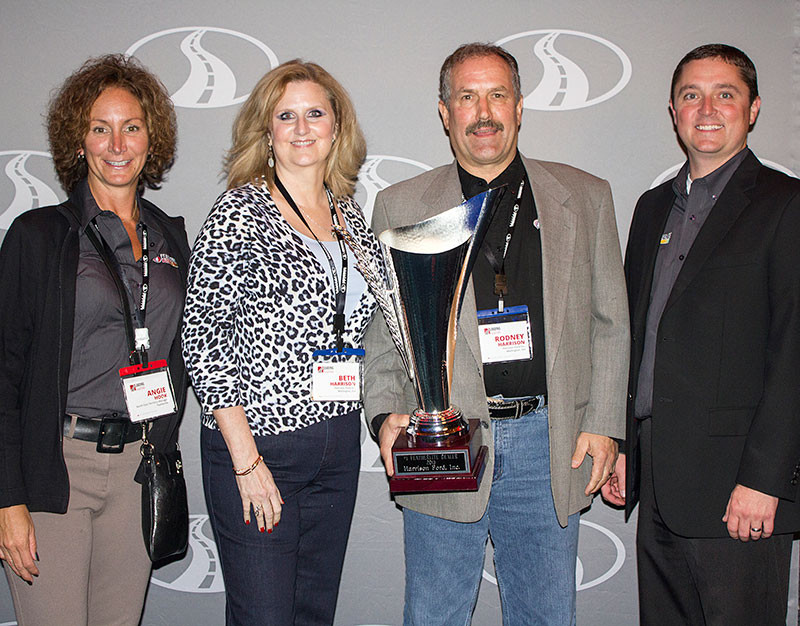 Featherlite Territory Manager Angie Hook (left) and National Sales Manager Justin Queensland (right) present Rodney and Beth Harrison of Harrison Ford with the Featherlite Cup Award, the award given to Featherlite's #1 Featherlite dealer, at the 2015 Dealer Meeting.