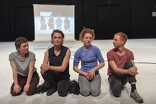 picture of four actors sitting in line on stage with white floor while projected on background.