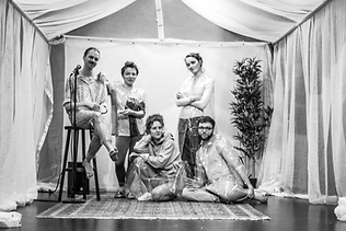 Black and white Picture of five actors positioned in a tent.
