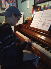 you male kid sitting and playing at the piano while reading sheet music