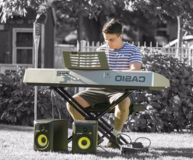 teen piano student sitting on bench reading sheet music while playing the piano fast
