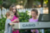 three kids standing around the keyboard outside with smiles on their face