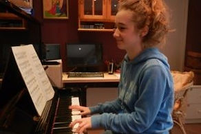 young female teen sitting at piano reading sheet music smiling