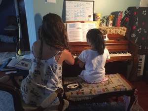 young female student sitting next to teacher on the bench while learning how to play piano