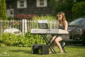 young female adult sitting playing keyboard outside on lawn reading sheet music during recital
