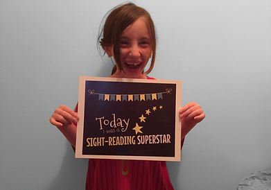 excited kid student holding award after completing easy piano song