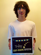 young male teen beginner piano student smiling holding award for being a sight reading superstar