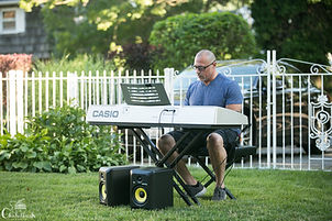 male adult beginner piano student sitting playing keyboard outside on lawn recital