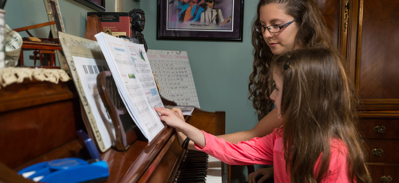 kid piano student pointing at a measure in the book for teacher to explain better