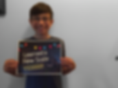 smiling kid piano student with glasses holding up award for learning a new scale