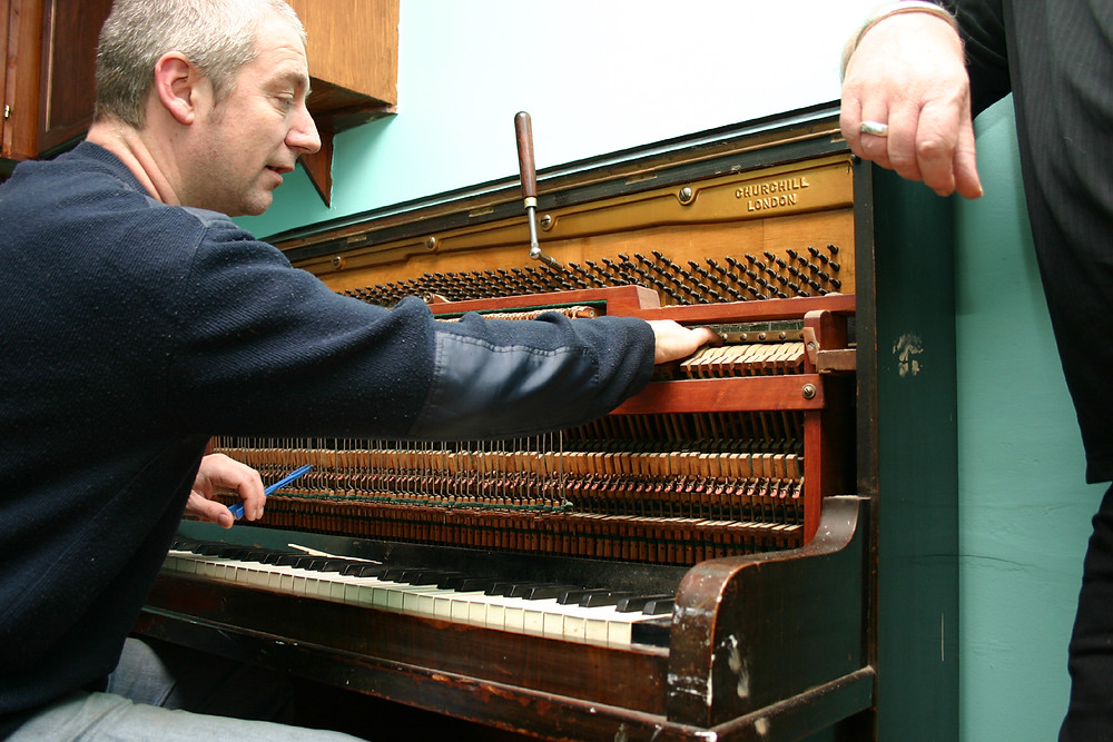 piano tuner in blue shirt tuning an open upright piano