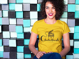 young female adult smiling against tiled background wearing yellow Chatalbash Lessons tshirt