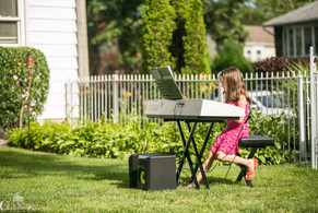 kid playing keyboard for family and friends at an outside recital performance