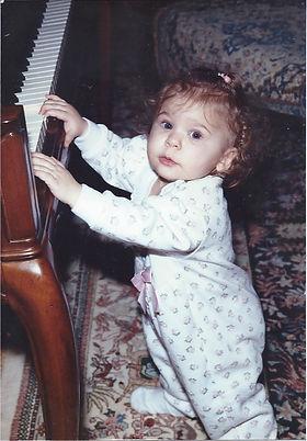 young female kid toddler in pajamas reaching up at piano keys smiling