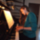 young female teen piano student sitting at piano reading sheet music