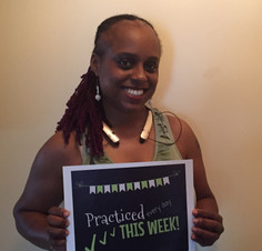 female adult beginner piano student smiling holding sign for practicing every day that week