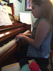 young female sitting at the piano reading and playing sheet music