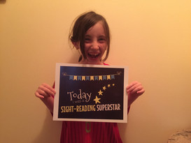 smiling girl student holding a piano award for being a sight reading superstar
