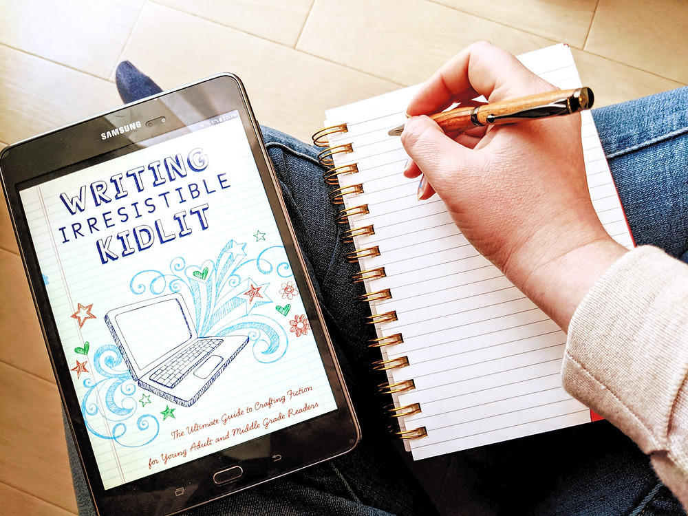 Image: The book Writing Irresistible Kidlit rests on a cross-legged lap next to a blank notebook page. A hand holding a pen is poised above the notebook, ready to write. | editsbytoni.com