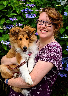 Editor Toni Suzuki holds her sheltie while standing in front of hydrangeas.